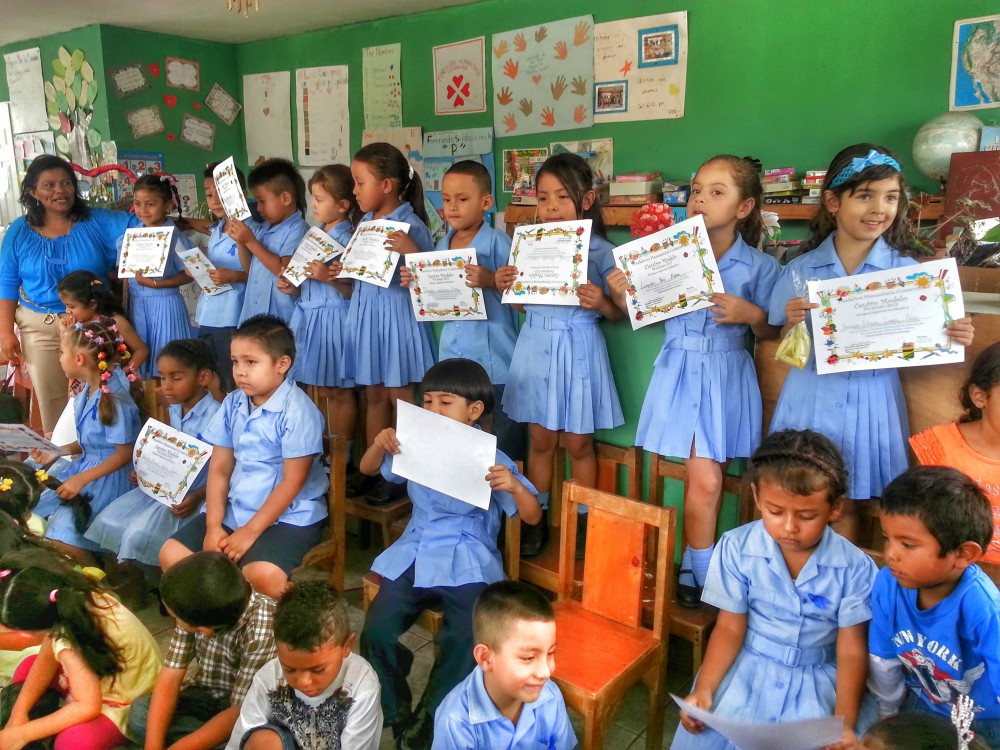 Children recently graduated from the Centro Modelo display their diplomas proudly in front of their parents.