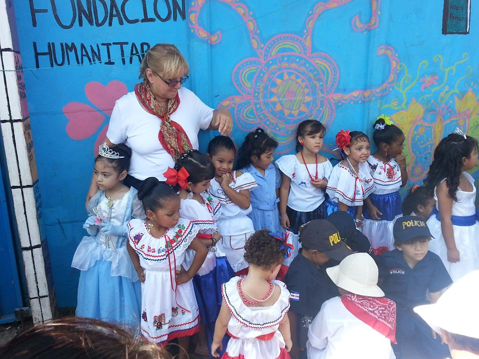 A few of the children with Gail Nystrom display their typical Costa Rican costumes in front of the Montesorri.