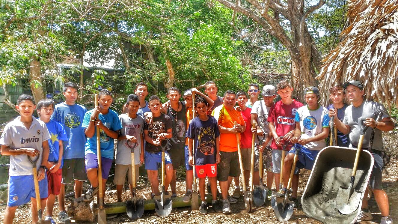 Some of the boys who are part of the soccer league help build a fence around the FInca.